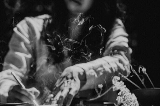 Black and white illustrative photo of woman writing with incense smoke and yarrow nearby