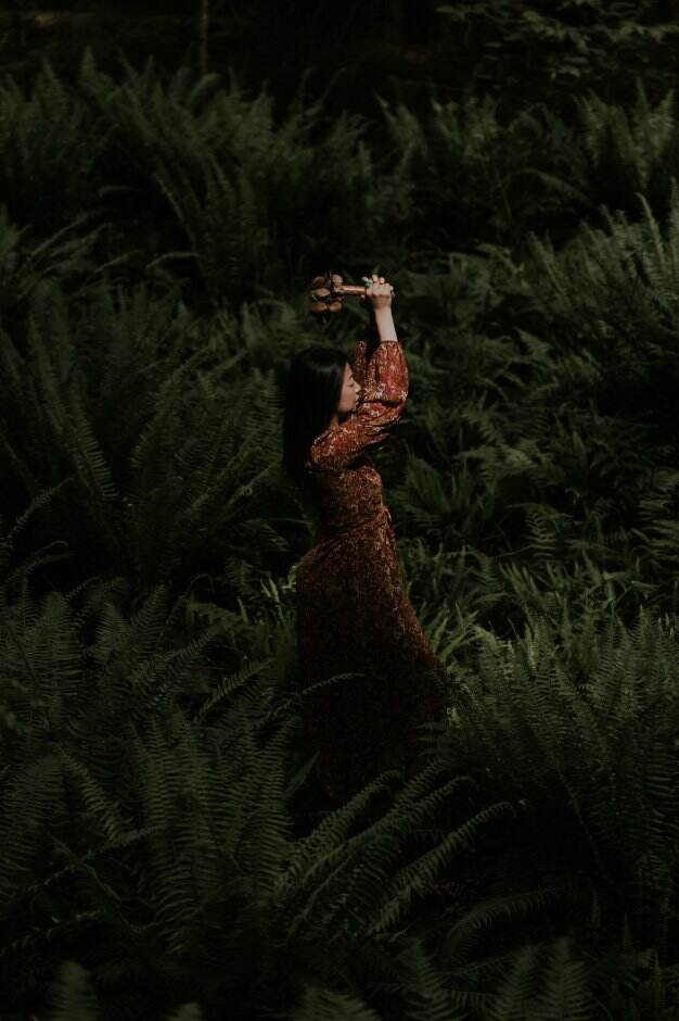 WOC in dark red dress standing in forest of ferns, holding a shamanic rattle