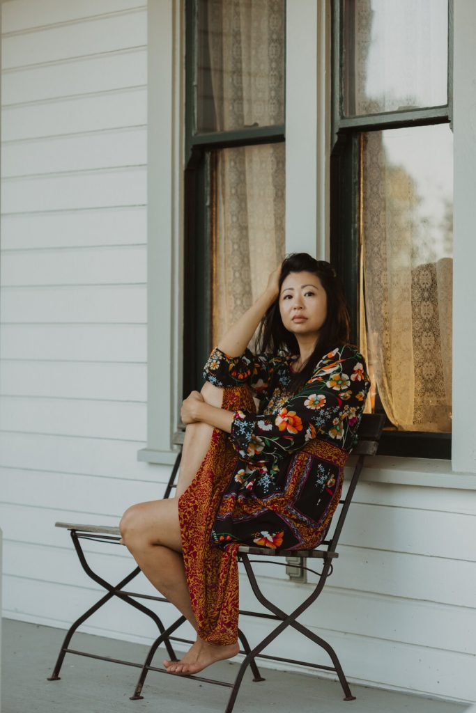 Mimi Young, wu shamanic intuitive and occultist, in floral dress sits on a bench on a porch