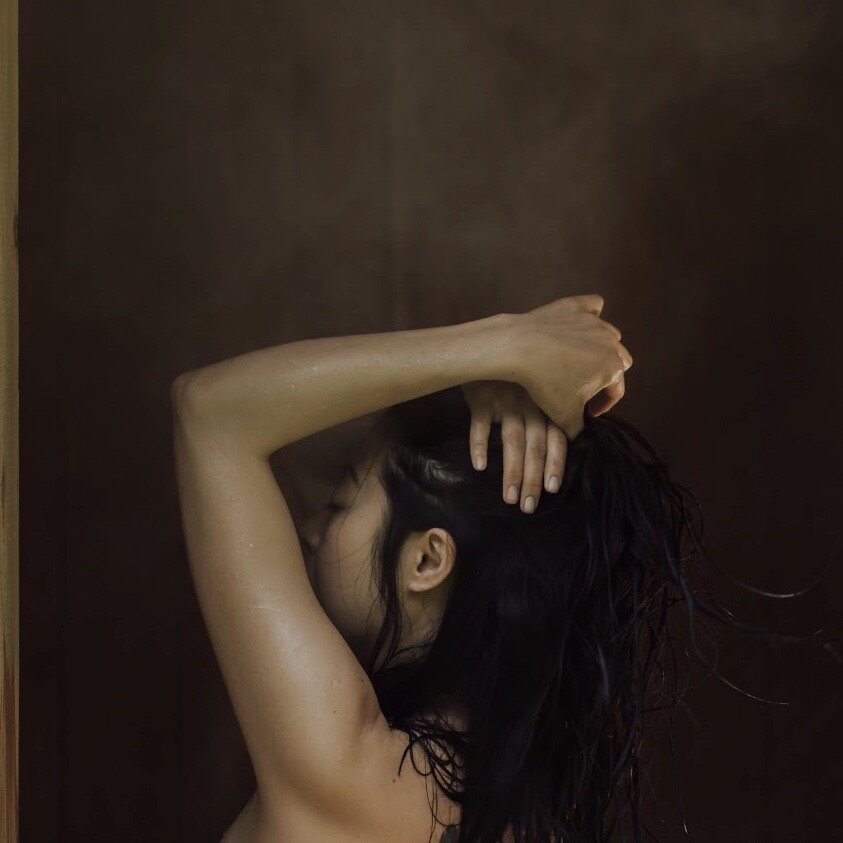 Asian woman's profile, holding her wet hair