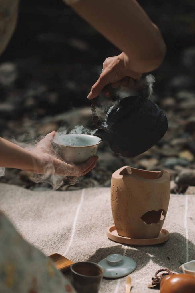 Hand holding the handle of a tea kettle pouring hot water into a gaiwan