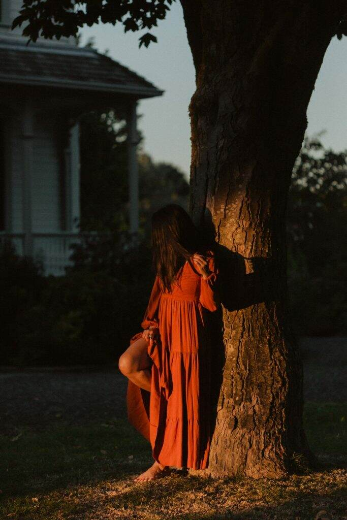 Woman of colour standing against a tree at golden hour