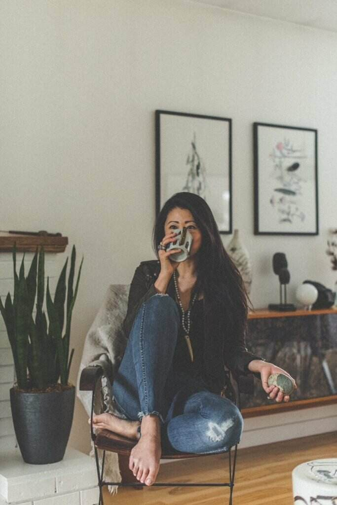 Woman of colour sipping out of a bug in a stylish living room with mystical tools in background