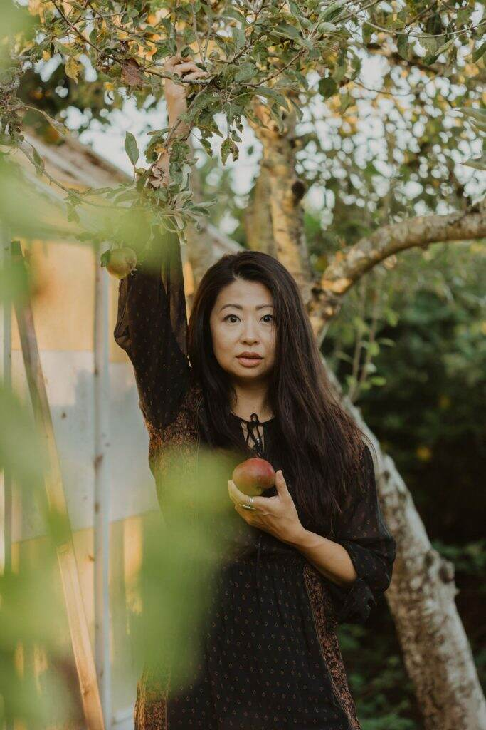 Asian woman holding apple standing in front of apple tree stares at the camera