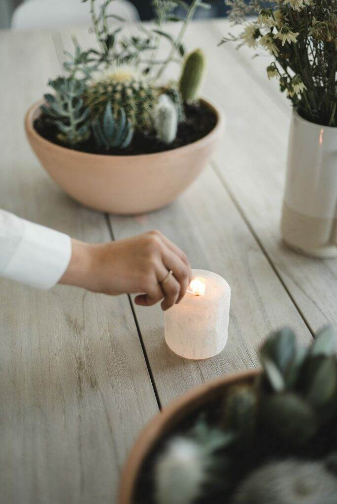 Hand holds match and lights up candle, with succulents in background