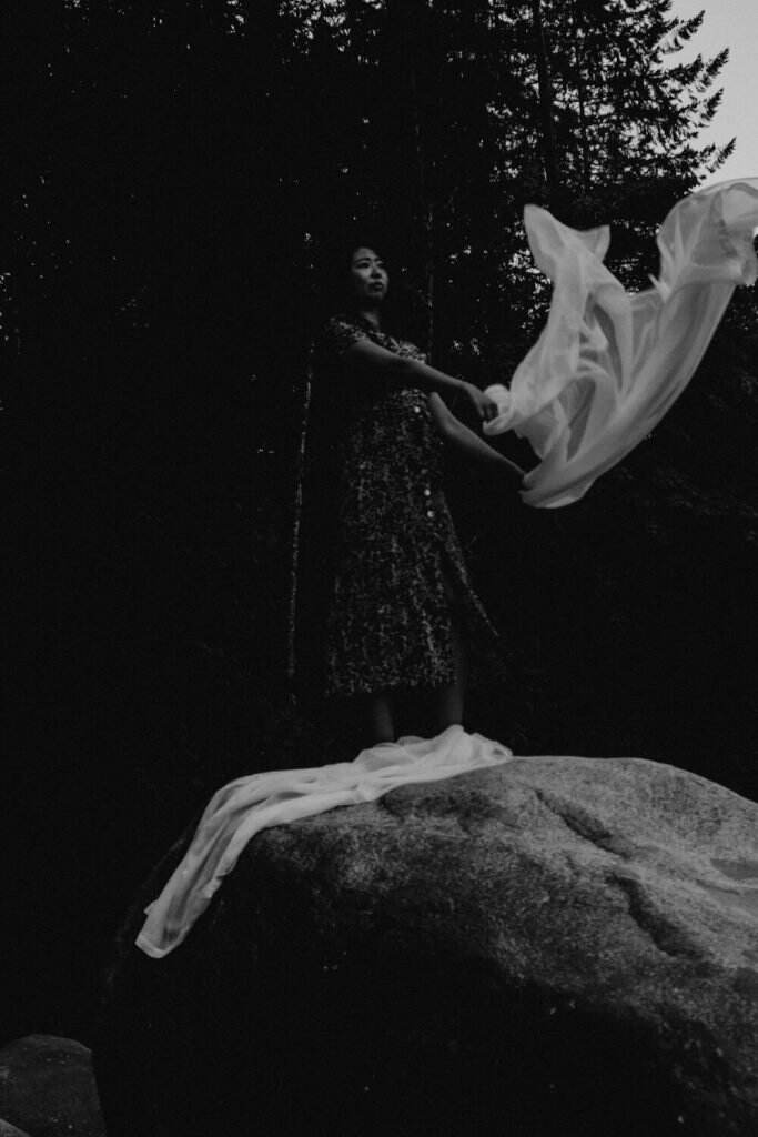 Woman holding back a veil with the forest as the backdrop
