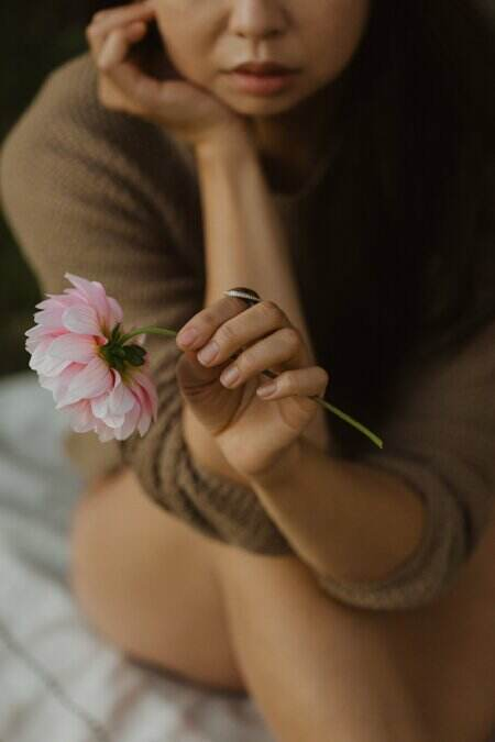 Asian woman's hand holding pink dahlia