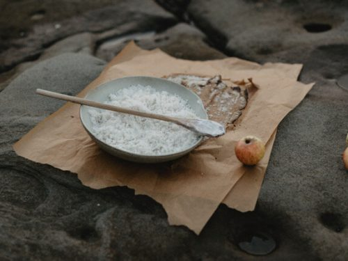 Plate of hand-rendered sea salt set on parchment paper, with apples in background on a picturesque stone surface.