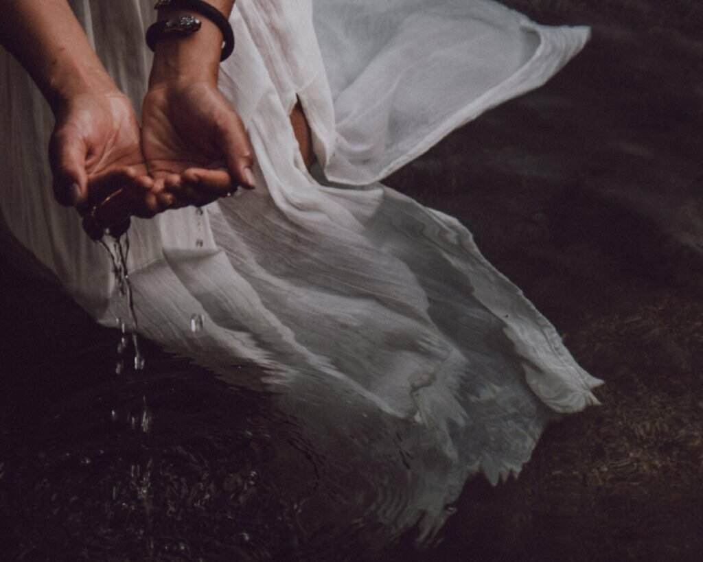 Woman of colour cupping water; her white dress flows with the water ripples, evoking the feeling of fluidity and mystery