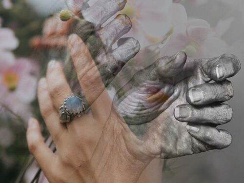 Layered hands of different ages, with flowers faded in the background