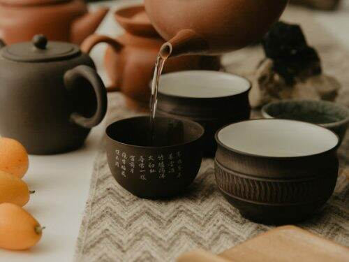 Artfully displayed traditional Chinese terracotta teaware. Teacup is pouring out oolong tea, with kumquats in the background.