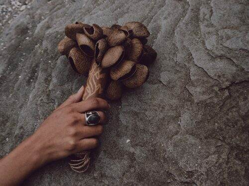 WOC with large ring holding a rattle for shamanic journeying against a textured stone background