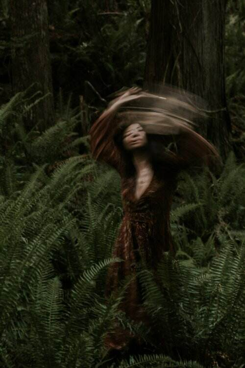 Moody image of blurred WOC in dark red dress in forest of ferns