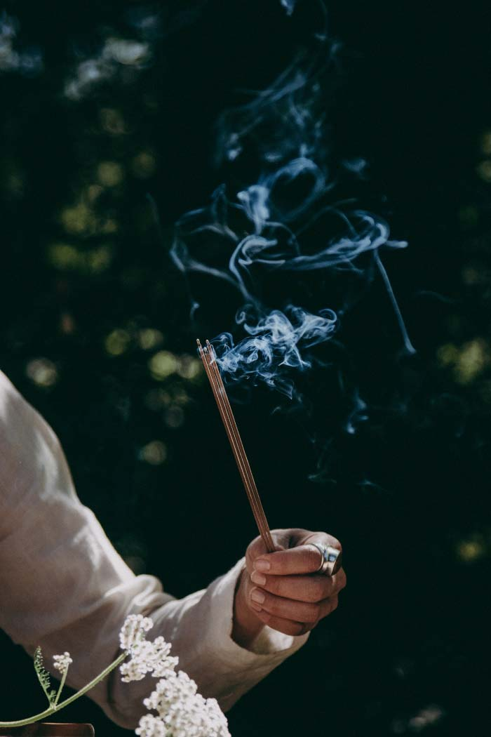 WOC holds several sticks of incense. Smoke wafts upwards in moody swirls
