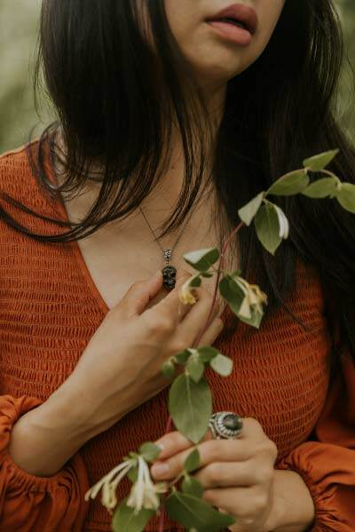 Mimi Young, wu shamanic intuitive and occultist holds honeysuckle blooms and stone skull pendant