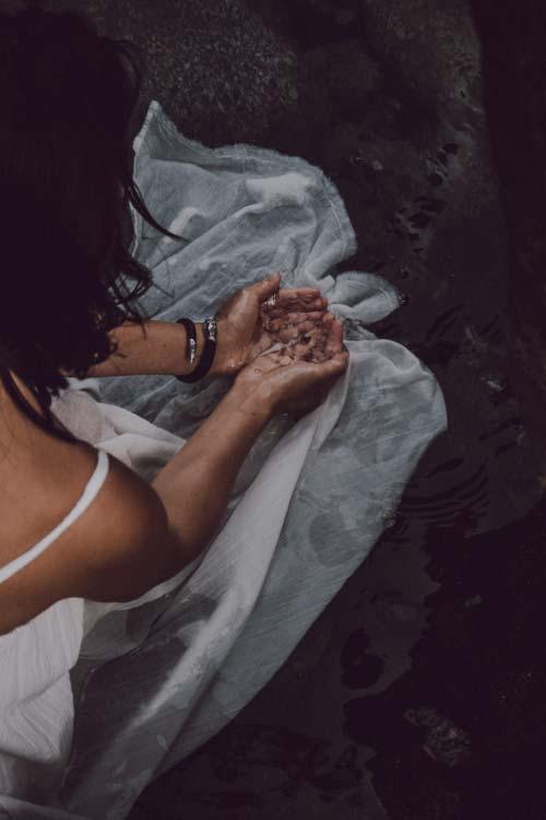 Hands feeling water, evoking a dreamy, moody feeling