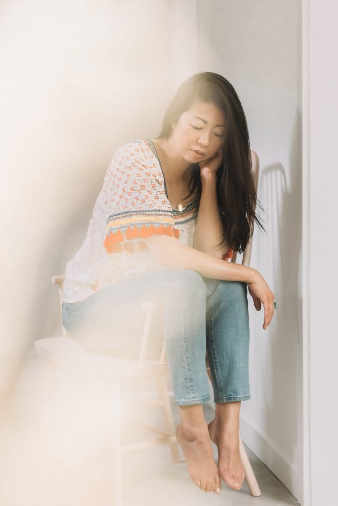 Han Taiwanese woman in jeans and boho top sits on chair and looks downwards