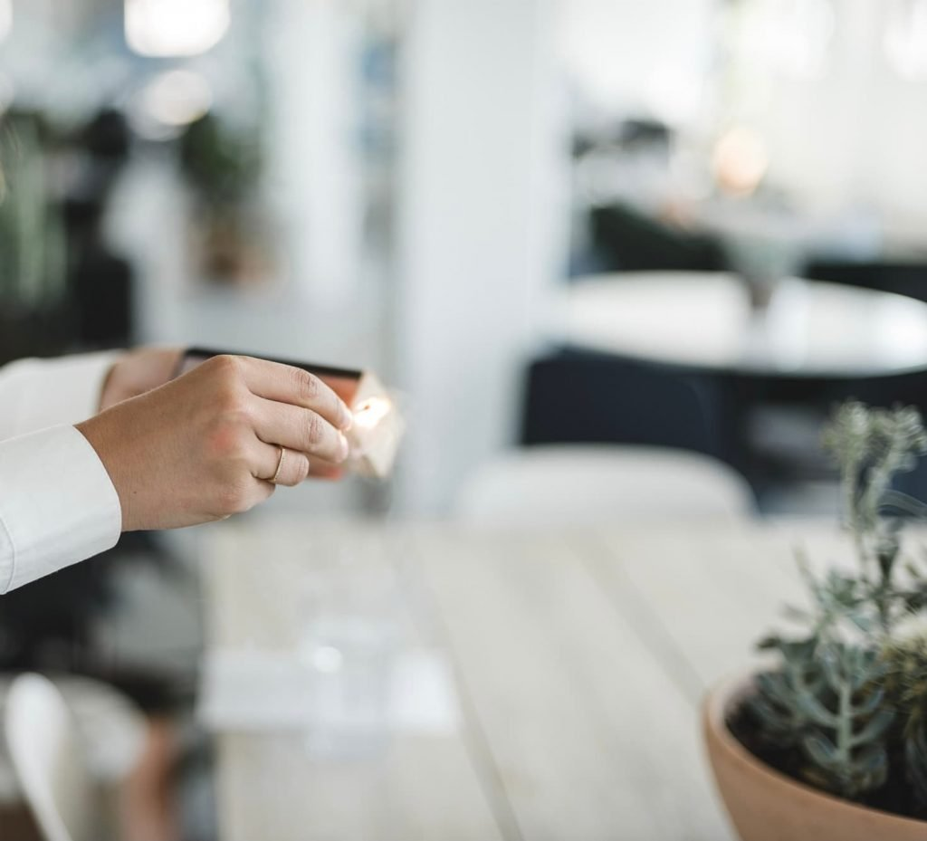 woman's hand wearing crisp white shirt strikes match against matchbox