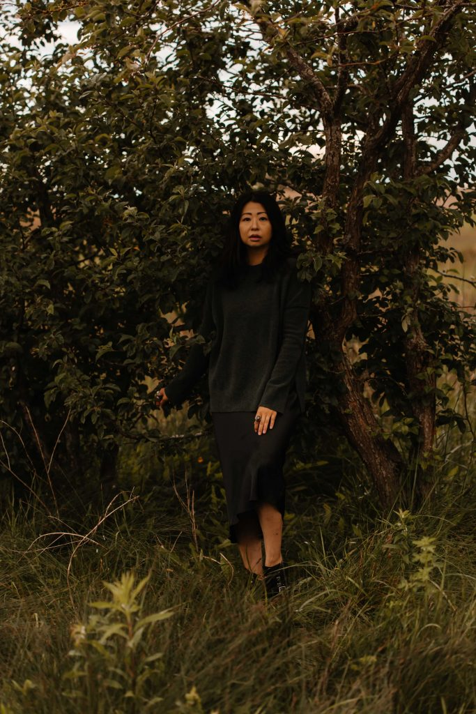 Taiwanese Canadian woman in green dress stands in front of tree