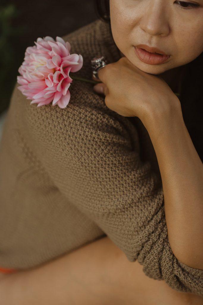 Taiwanese Canadian woman wearing flax coloured wool sweaterholds pink dahlia