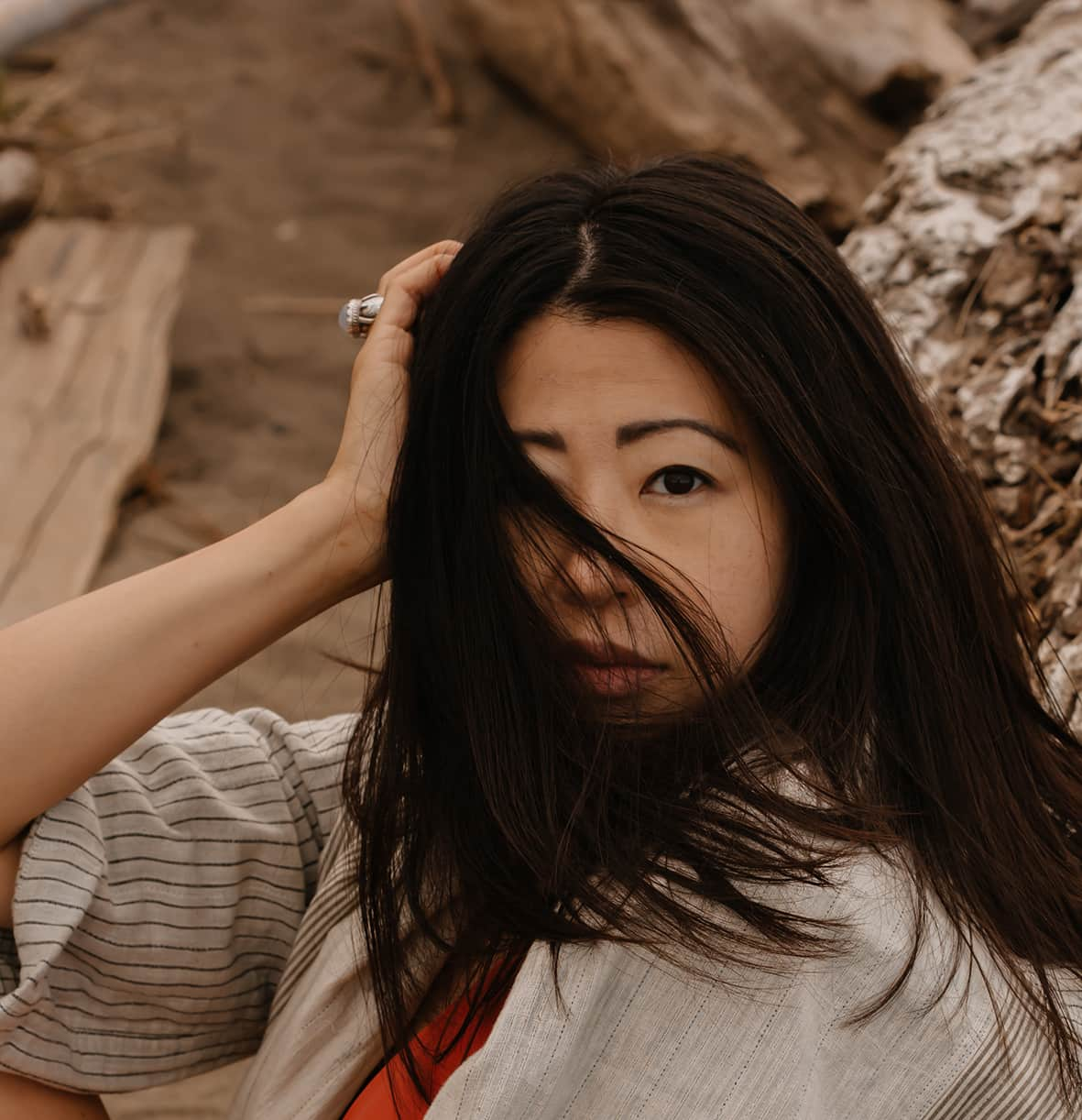Portrait of Taiwanese Canadian woman while sitting at beach, with wind blown into her face