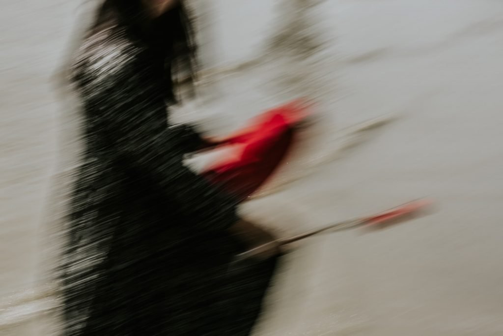 Taiwanese woman in black dress holding a red core shamanic drum, rendered in an artistic blur