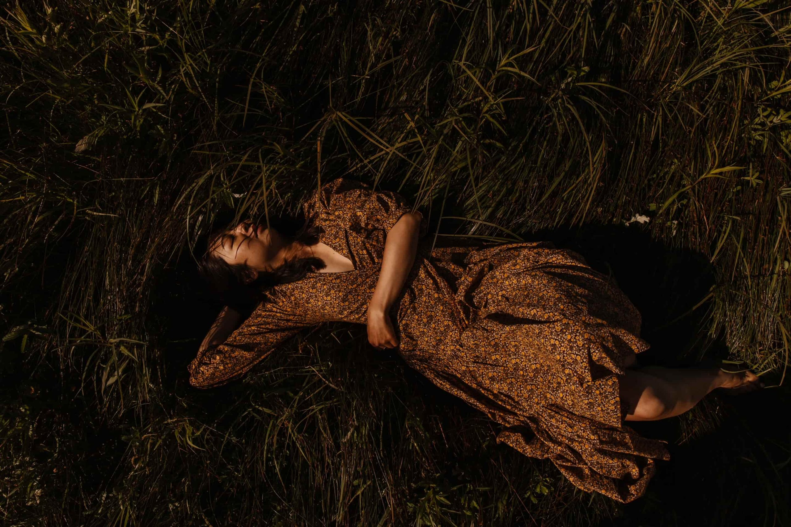 Taiwanese Canadian woman in golden-brown calico dress lies in grass