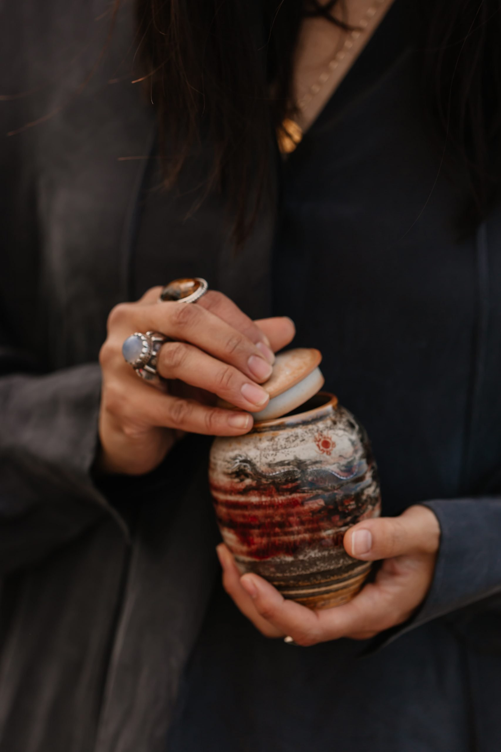 Asian woman's hands holds a ceramic jar filled with magickal energy