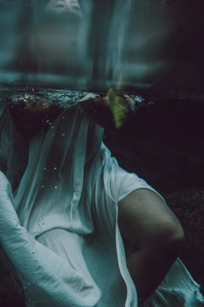 Woman of colour in white dress photographed under the water artfully, evoking dreams